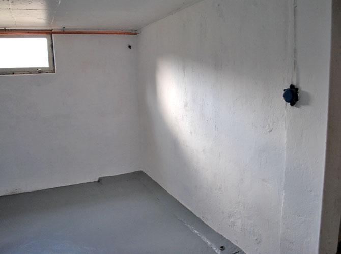 Källarförrådet efter. Vitmålade väggar och gråmålat golv.